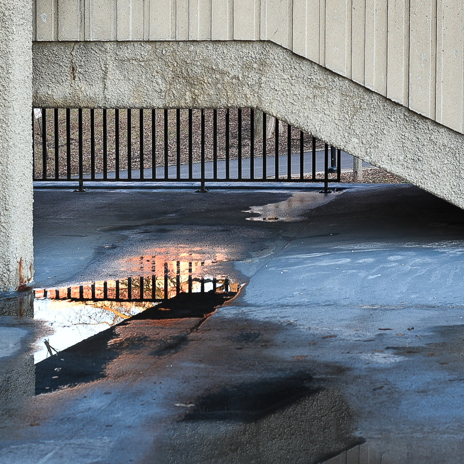 Water puddle reflecting sunlight under Concrete staircase
