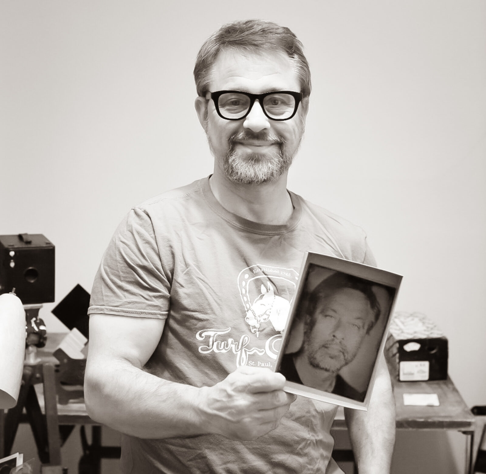 Man looking in the camera holding a tintype photograph of himself