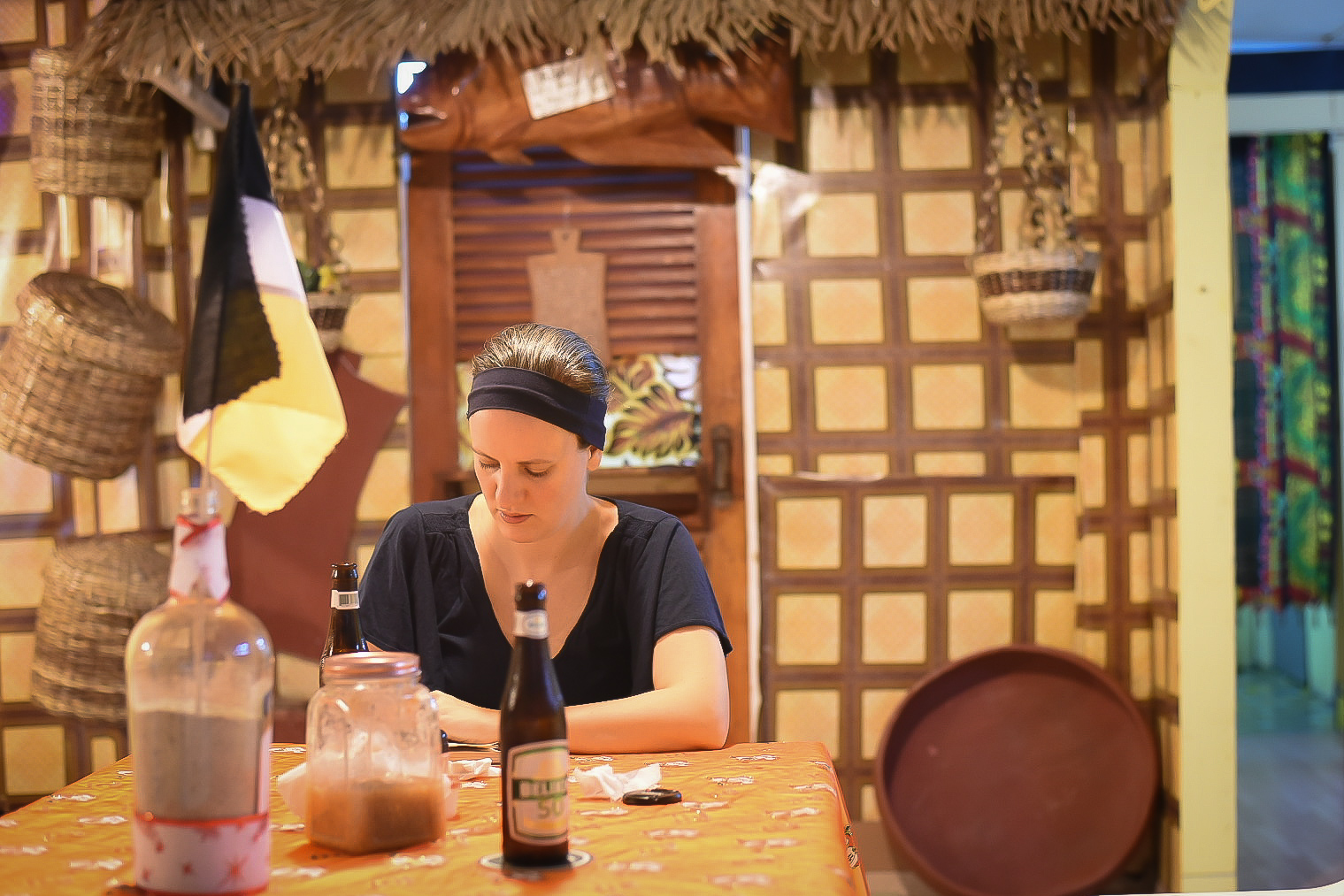 Woman sitting at a dining table in a Garifuna restaurant in Belize writing in a journal