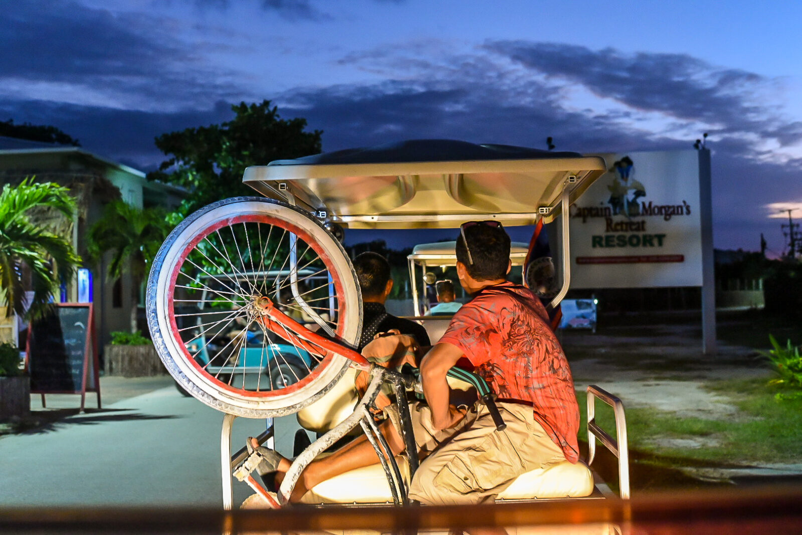 Man clinging to a bicycle on the back of a golf cart at sundown passing Captain Morgan's Retreat Resort