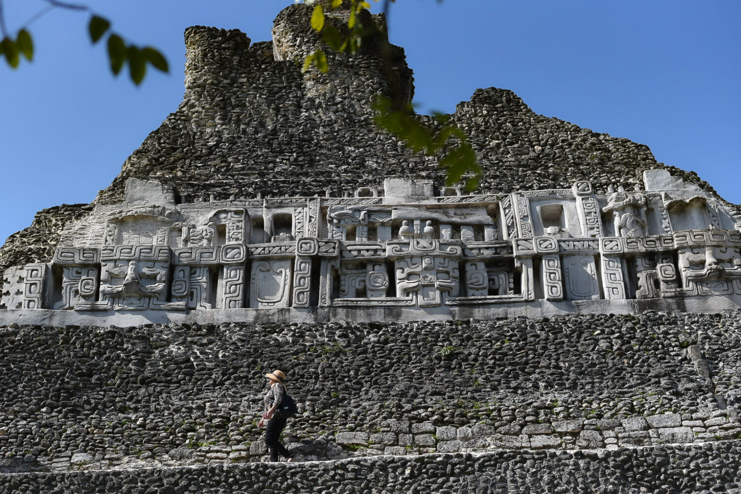 """A frieze replicated artifact depicting gods and monsters. At the foot of """"El Castillo,"""" name given to this mammoth of a structure, is where the ghost of the stone maiden, Xunantunich, was encountered by nearby villagers in early 1800."""