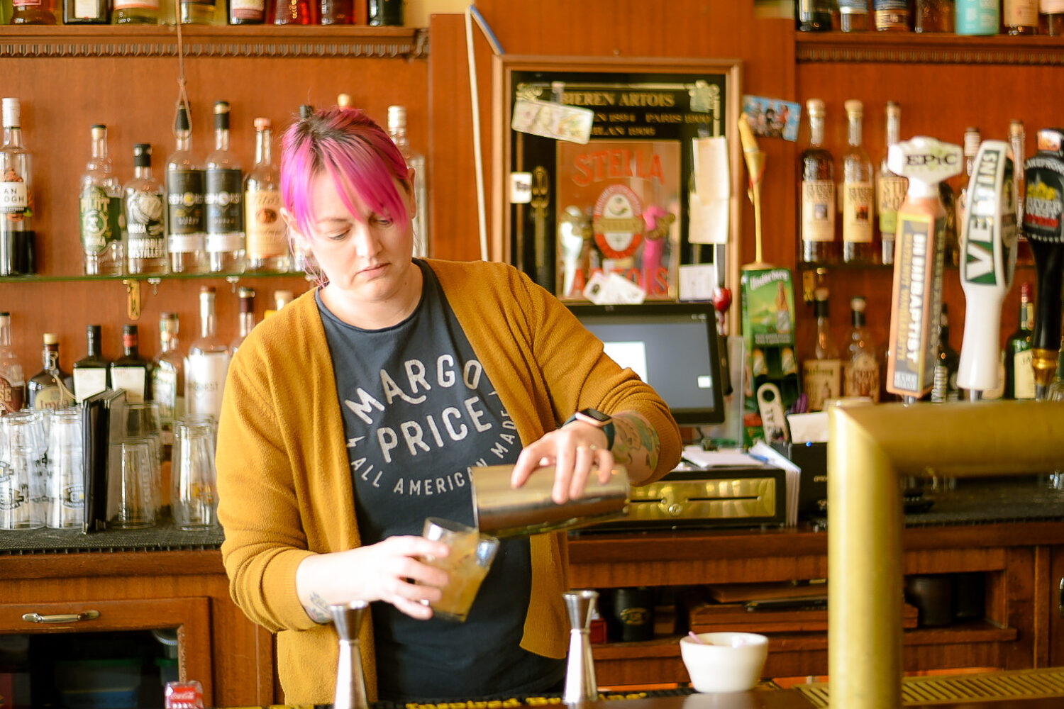 woman with pink hair behind a bar pouring a drink from a metal shaker into a tumbler glass