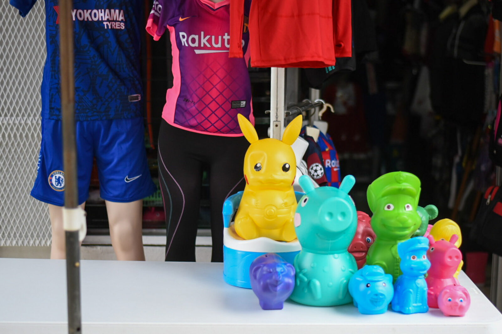 plastic pikachu and a variety of cartoon figures displayed on a table at a street market