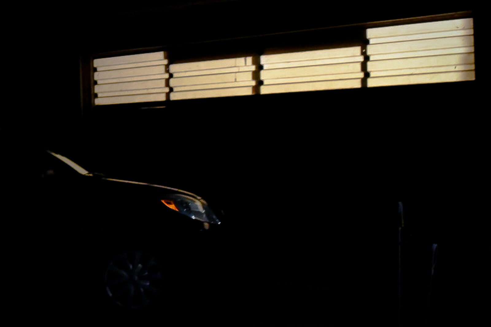 a car parked in front of garage door at night