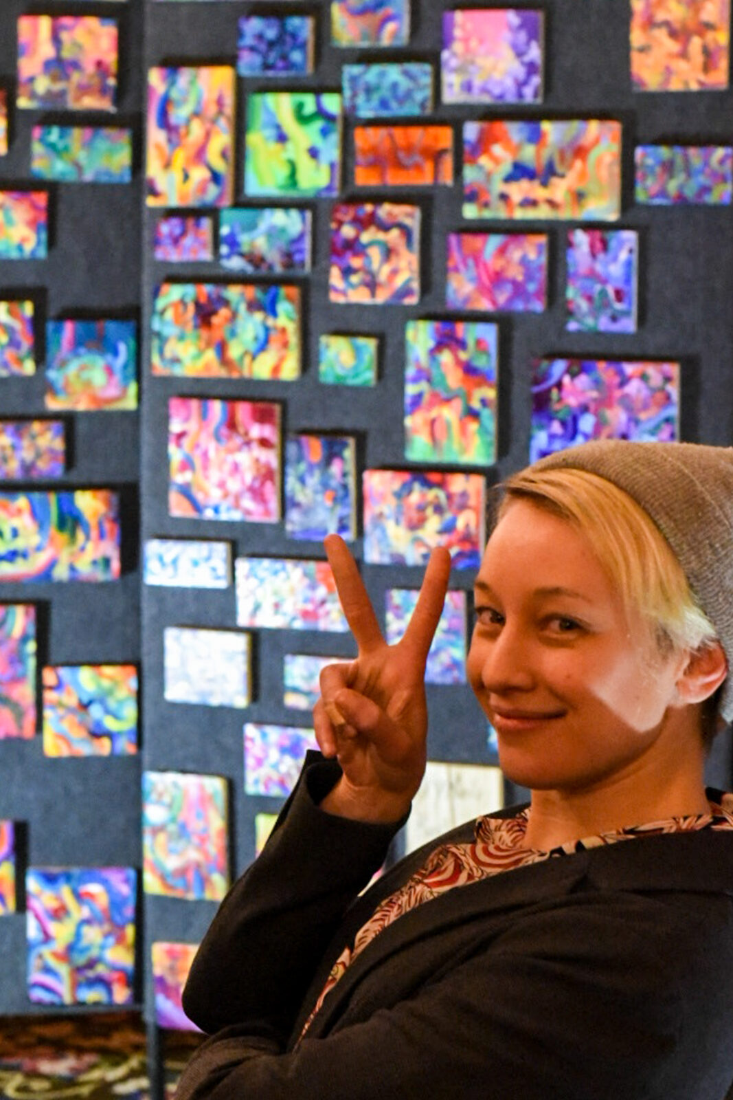 Person posing holding up a peace sign standing in front of a display of artwork