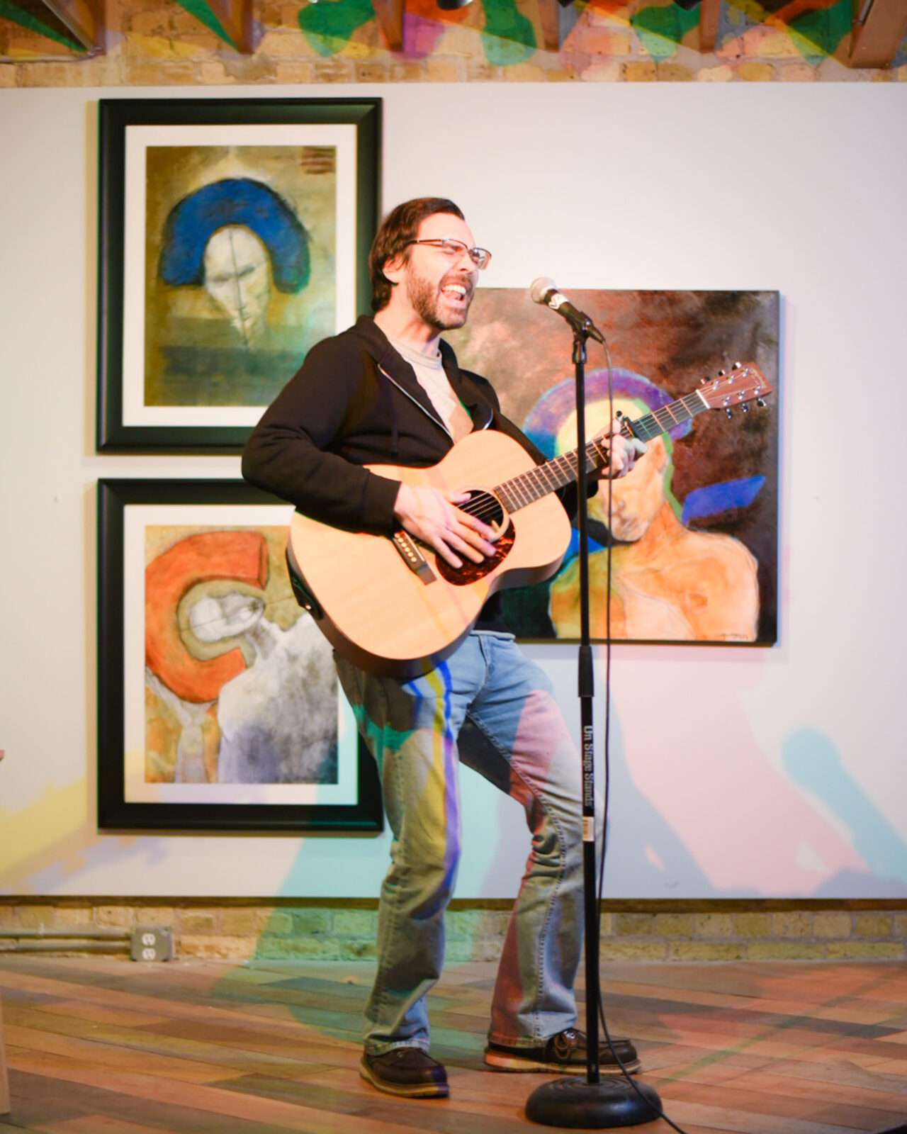 man in spotlit stage behind a microphone on a stand holding a guitar