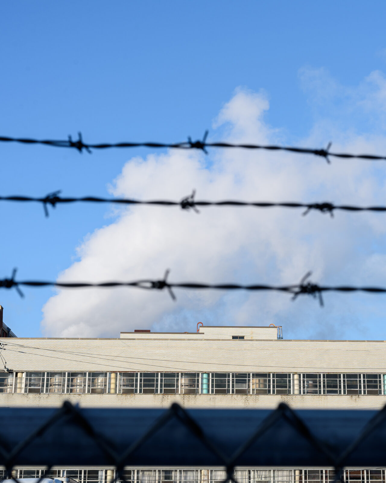 blue sky with fluffy cloud over a building roof behind chain link fence