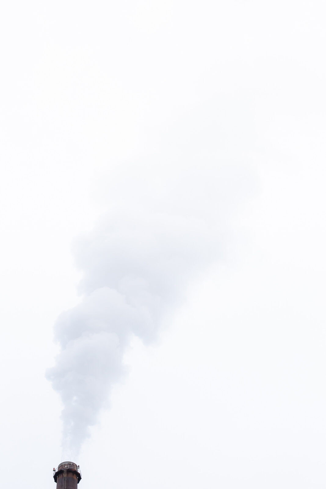 water vapor coming out of a chimney with a white and grey sky in the back