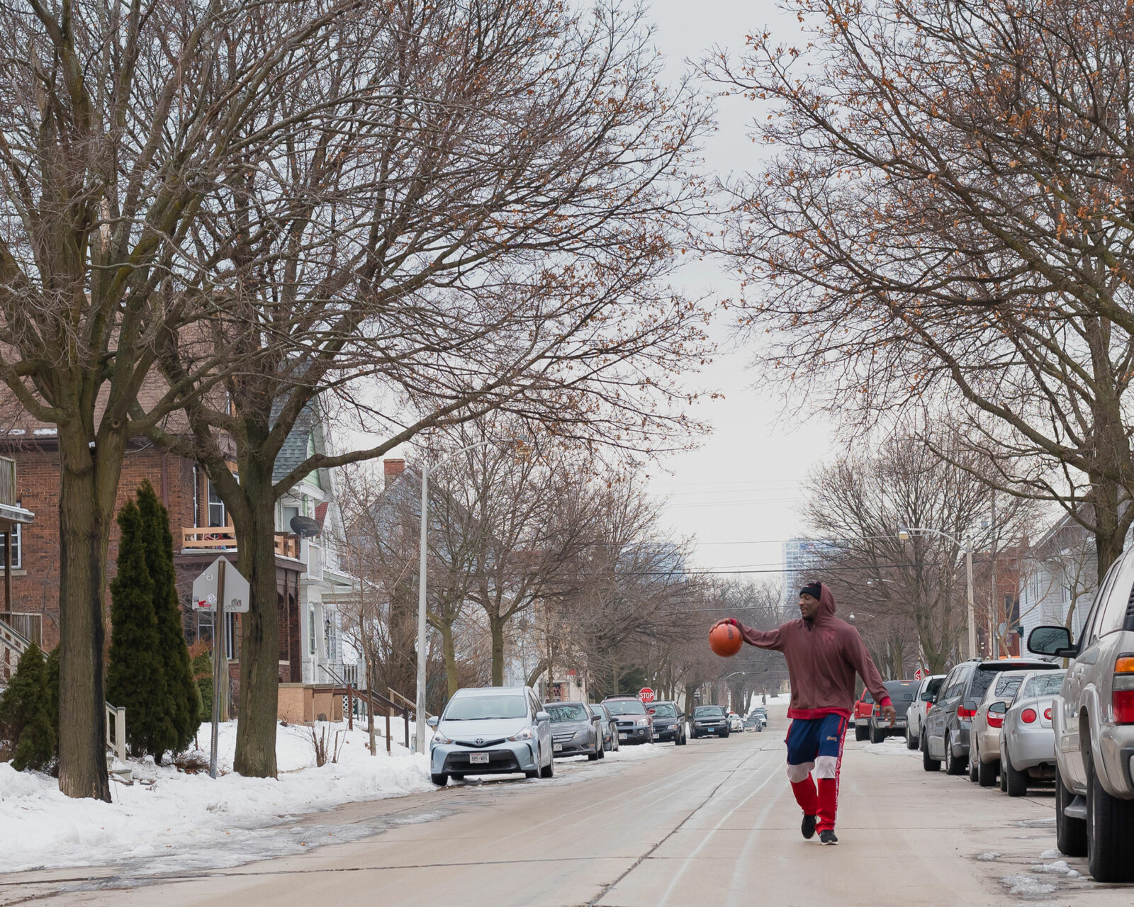 a man in the middle of a neighborhood street with a basketball